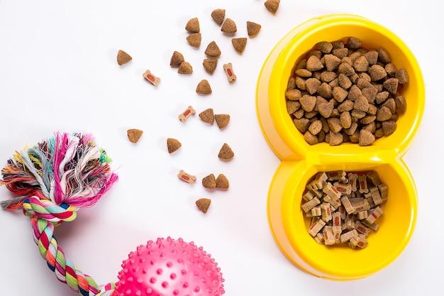 Sucha karma dla zwierząt w misce i zabawki dla psów na białym tle widok z góry