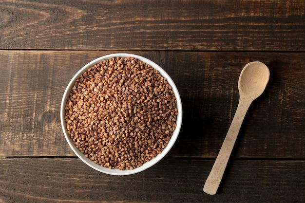 Sucha kasza gryczana w białej misce z łyżką na drewnianym brązowym stole. płatki. zdrowe jedzenie. owsianka. widok z góry