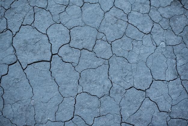 Sucha popękana szara ziemia.