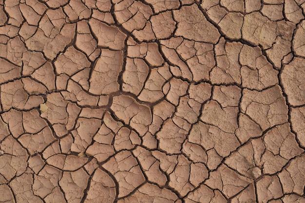 Sucha popękana ziemia w porze deszczowej, ponieważ brak deszczu braku tekstury popękanej wody