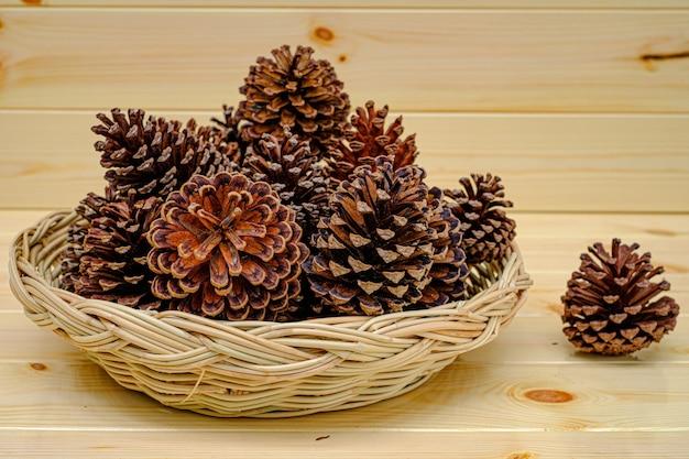 Sucha szyszka sosnowa umieszczona w tacy na drewnianym stole