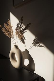 Sucha trzcina pampasowa w stylowym wazonie. cienie na ścianie. sylwetka w świetle słonecznym