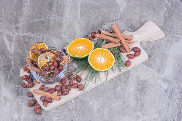 Suche biodra i plastry pomarańczy ze świeżych pomarańczy na desce.