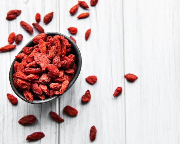 Suche czerwone jagody goji dla zdrowej diety na starym drewnianym tle