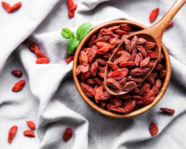 Suche czerwone jagody goji dla zdrowej diety na stole z tkaniny