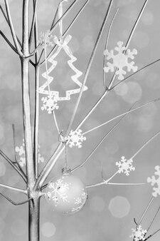 Suche drewno pomalowane na srebrno i ozdobione płatkami śniegu, bombką i zabawką jako choinka na neutralnym tle.