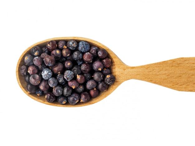 Suche jagody jałowca w drewnianą łyżką na białym tle.