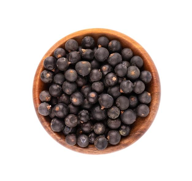 Suche jagody jałowca w drewnianej misce, na białym tle.