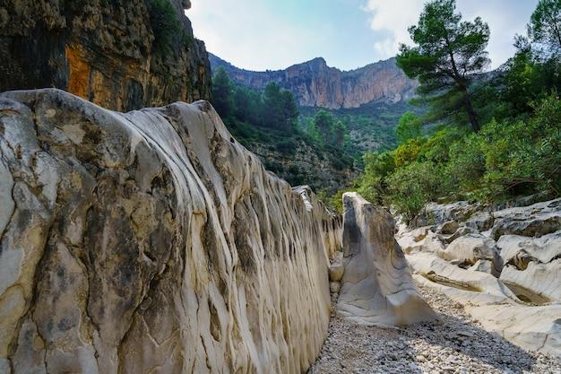 Suche koryto rzeki między górami z dużymi zerodowanymi skałami.