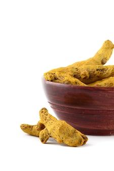 Suche korzenie kurkumy lub kora w drewnianej misce na białym tle