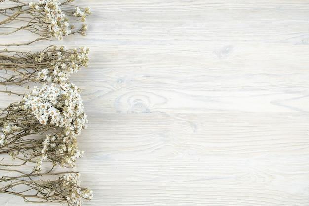 Suche kwiaty rumianku na drewnianej desce. widok z góry, miejsce na kopię