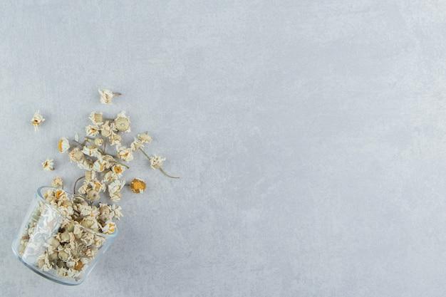 Suche kwiaty rumianku w szklanej misce.