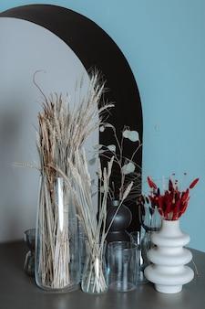 Suche kwiaty w wazonach stojące na drewnianym stole na tle niebieskiej ściany z łukiem jesienna kompozycja dekoracyjna vertical