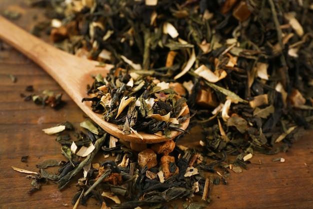 Suche liście herbaty z łyżeczką na drewnianym stole