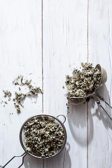 Suche liście malin w zbliżenie sitko do herbaty alternatywnych leków ziołowych