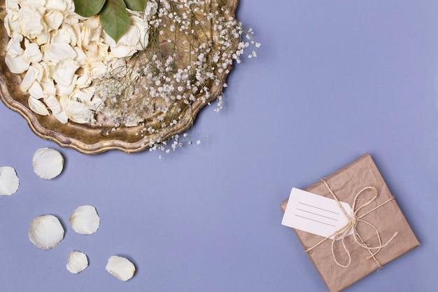 Suche płatki białych róż i gipsówki na pięknej antycznej tacy, prezent zawinięty w papier rzemieślniczy na niebieskim tle. miejsce na tekst.