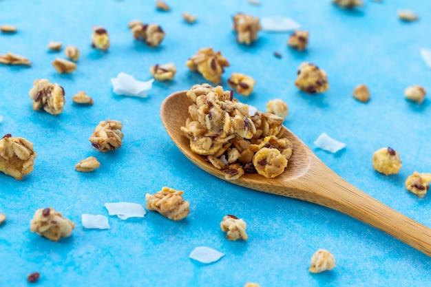 Suche płatki śniadaniowe. chrupiąca miodowa granola z ziarnami lnu, żurawiną i kokosem w drewnianej łyżce na niebieskim tle. zdrowe i bogate w błonnik jedzenie