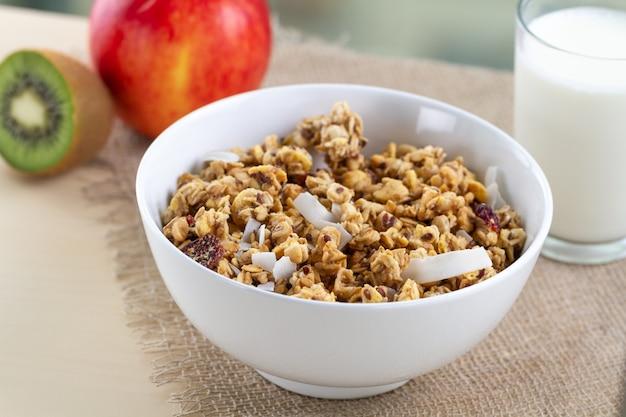 Suche płatki śniadaniowe. chrupiąca miodowa miska musli z nasionami lnu, żurawiną i kokosem oraz szklanką mleka na stole. zdrowe i bogate w błonnik jedzenie. czas na śniadanie