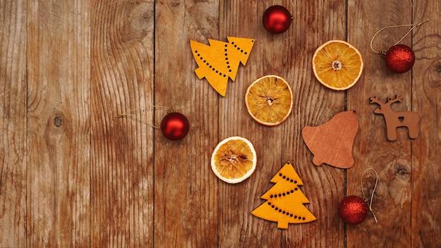 Suche pomarańcze, czerwone kulki i drewniane figurki świąteczne na rustykalnym brązowym drewnianym tle z miejscem na tekst