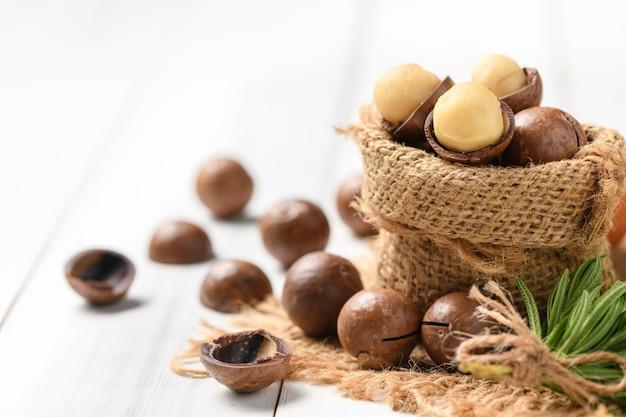 Suche prażone orzechy makadamia w worku na białym tle drewna