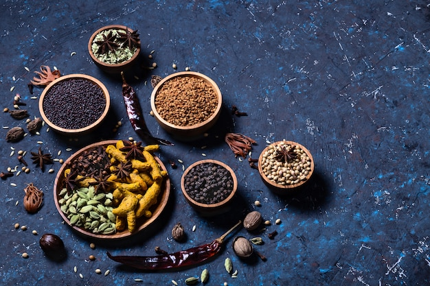 Suche, rozgrzewające indyjskie przyprawy susz w drewnianych miseczkach
