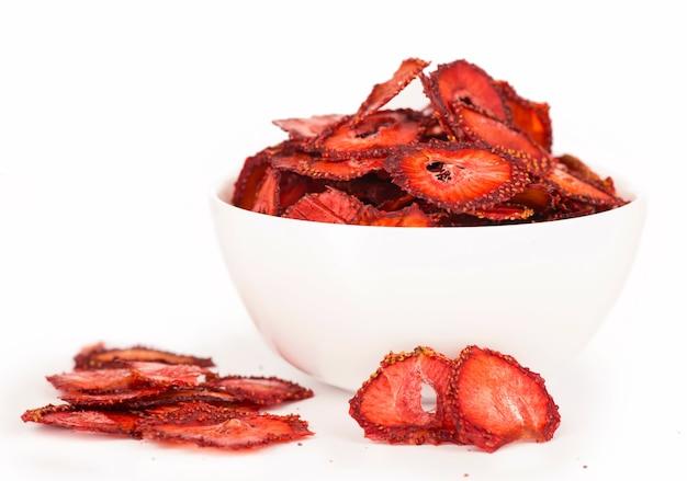 Suche truskawki w białej płytce, chipsy truskawkowe na białym tle