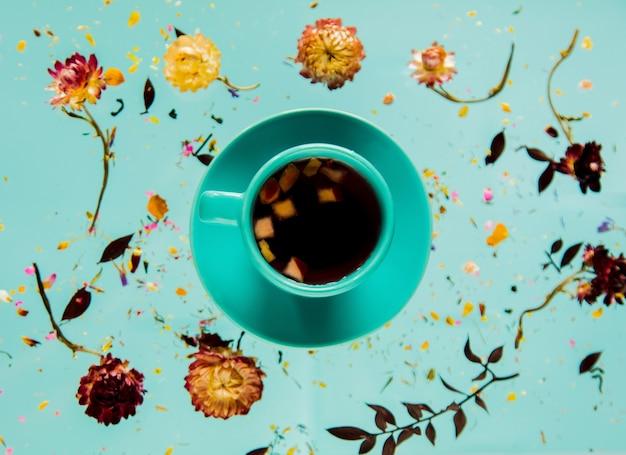 Suche ziele bellis z kwiatami i filiżankę herbaty jabłkowej na niebieskiej powierzchni na białym tle. bez cieni