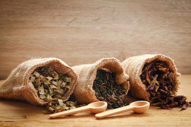 Suche zioło do picia w małej brązowej torbie worek umieszczonej na drewnianej podłodze.