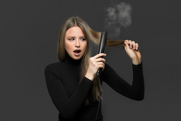Suche zniszczone włosy spalone koncepcją żelazka do włosów. młoda dziewczyna trzyma żelazko do włosów spalanie jej włosy.