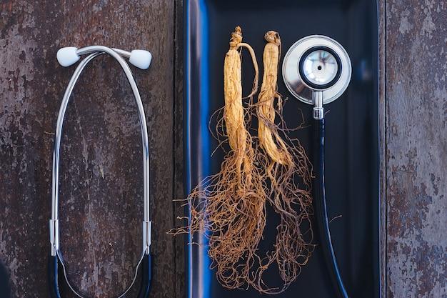 Suchy ginseng na czarnym talerzu z stetoskopem na drewnianym tle