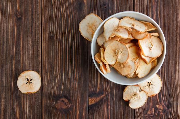 Suchy jabłko w pucharze na drewnianym tle. widok z góry. miejsce na tekst