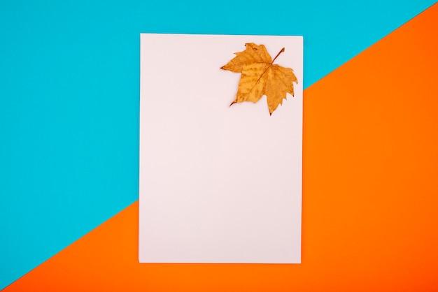 Suchy liść na niebieskim i pomarańczowym tle z pustym folio