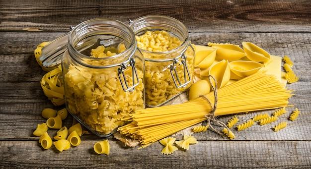 Suchy makaron w puszkach i wymieszany ze spaghetti. na drewnianym stole.