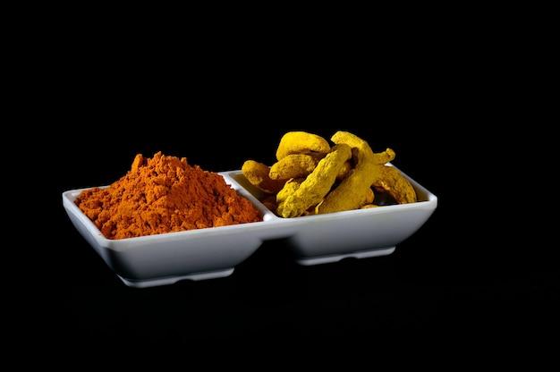Suchy proszek z kurkumy i korzenie lub kora na białym talerzu