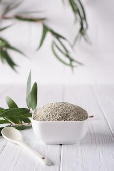 Suchy puder z glinki do twarzy w misce. naturalni kosmetyki dla domu lub salonu zdroju traktowania na białym tle