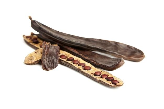 Suchy strąk chleba świętojańskiego z nasionami na białym tle