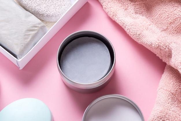 Suchy szampon w postaci stałej na różowym stole, z bliska