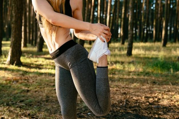 Suczka w legginsach i podkoszulek, rozciągająca nogi, trening w parku.