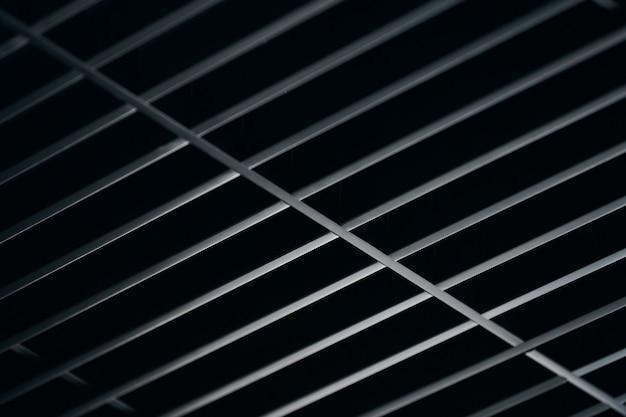 Sufit kratki biurowej. nowoczesny sufit z metalową kratką w kolorze czarnym, podwieszane pokrycie. streszczenie tekstura.