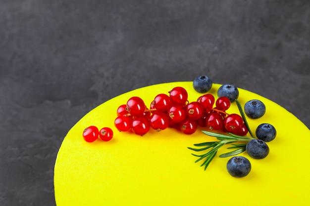 Sufletowe cytrynowe żółte ciasto ozdobione jagodami i czerwoną porzeczką