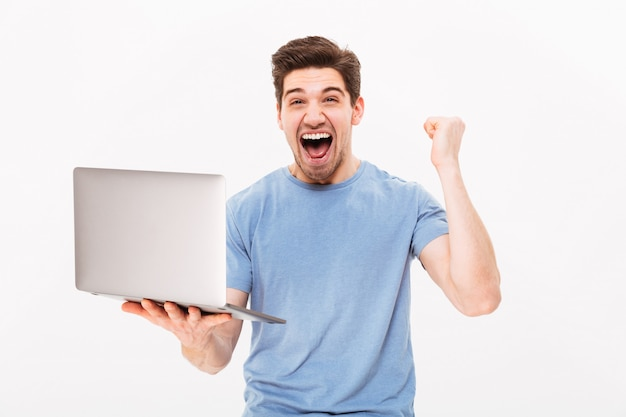Sukces brunetka facet w koszulce, zaciskając pięść i radując się jak szczęśliwy facet lub zwycięzca podczas korzystania z laptopa, na białym tle nad białą ścianą