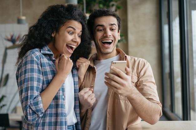Sukces celebracja szczęśliwa para emocjonalne. podekscytowani znajomi korzystający ze smartfona, grający w gry wideo