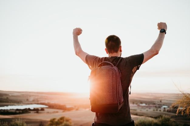 Sukces człowieka z podniesionymi rękami stojący na szczycie góry podczas zachodu słońca. piesze wycieczki i przyroda