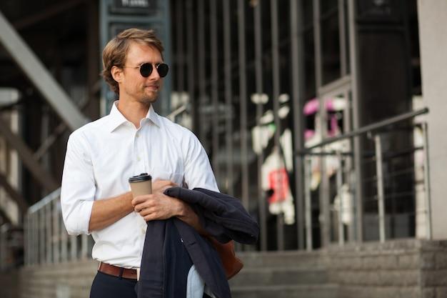 Sukces i chudy dyrektor generalny pije kawę na ulicy podczas przerwy