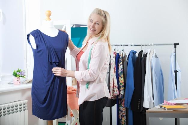 Sukces kobiety projektant ubrań, krawiec w studio w pełnym rozwoju.