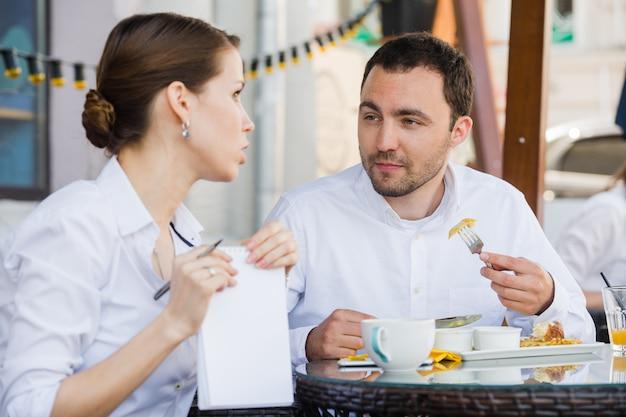 Sukces menedżera siedzącego na lunchu z kolegą i udzielającego jej instrukcji