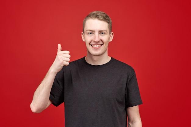 """Sukces młodego biznesmena w czarnej koszulce pokazuje """"doskonałe"""". śnieżnobiały, duży uśmiech wskazuje na świetnego dentystę i że sprawy idą w górę."""