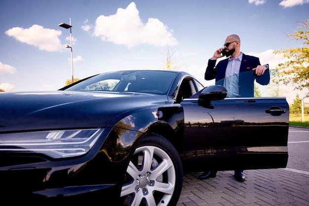 Sukces młodego człowieka z telefonem w pobliżu samochodu na parkingu.