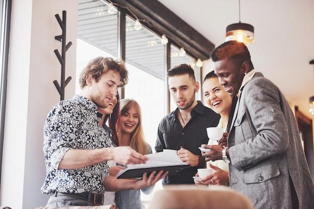 Sukces młodych ludzi biznesu mówi i uśmiecha się podczas przerwy na kawę w biurze