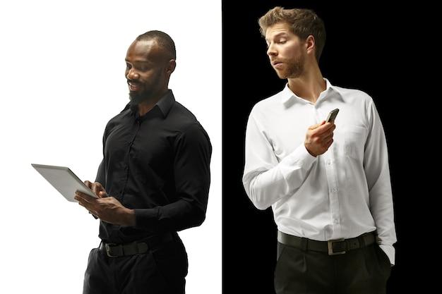 Sukces szczęśliwych mężczyzn afro i kaukaskich. mieszana para z gadżetem. dynamiczny obraz męskich modeli na białym i czarnym studio. koncepcja ludzkich emocji twarzy.